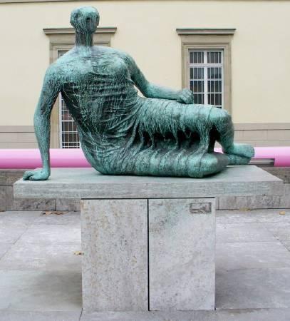 亨利‧摩爾,《穿衣的斜倚女人》,1957–58年。