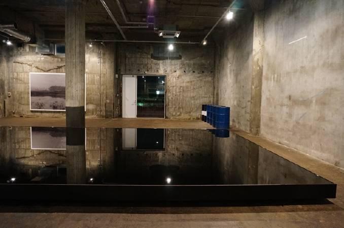 由港灣倉庫改建而成的BankART Studio NYK,空間性格極適合當代藝術展出。前方為日本藝術家原口典之(Noriyuki Haraguchi)的油池作品。