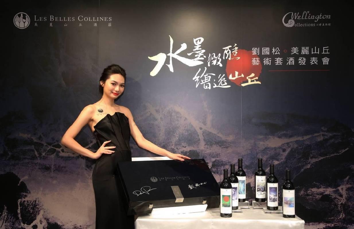 model展示美麗山丘套酒及簽名鋼琴烤漆酒盒,酒標畫作由左至右依序為《誰說紅葩夏日芳》《吹皺的山光》《諾布朗瀑布》《山奇水亦奇》《夜靜雪山空》《漪》