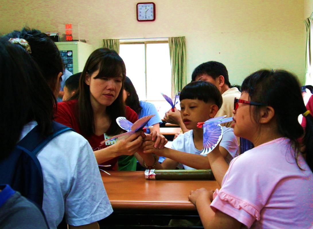 參與活動家長與孩子在科博館指導下製作紙飛鳥(經當事人同意拍照使用)
