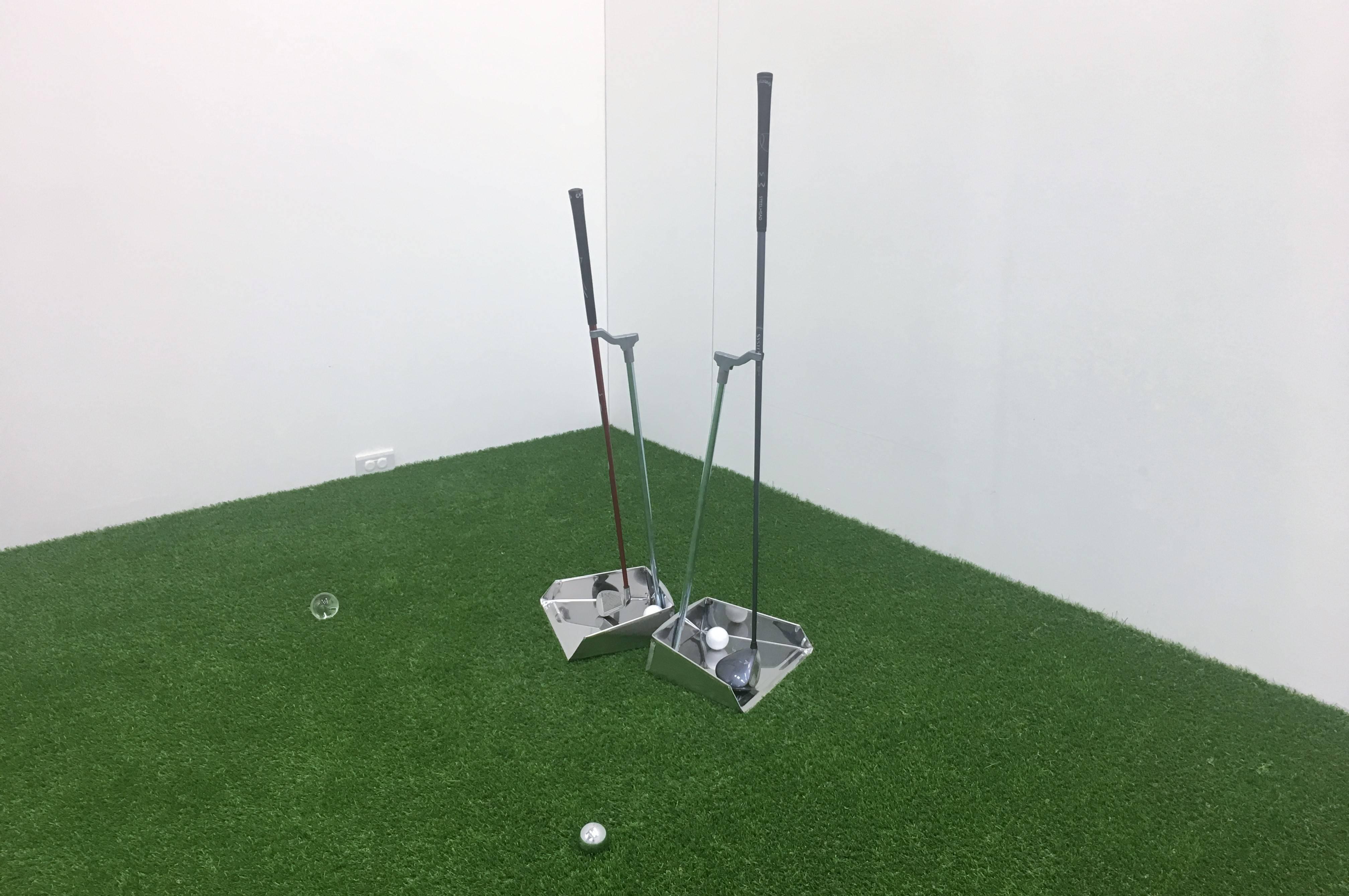 【在放鬆的多數的陽光下】李明學個展 李明學,《練習曲》,畚箕、高爾夫球杆、球體、人工草皮,948x699x469 cm,2019。
