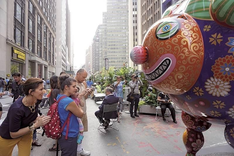在紐約百老匯街頭,遊客十分喜愛與笑臉迎人的《三羊開泰》之作。(攝影/林亞偉)