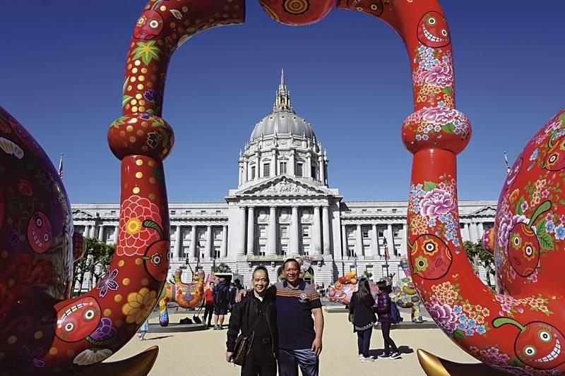 印象畫廊負責人歐賢政,與洪易在《分享象》作品合影。《分享象》,已經行遍日本、台灣到美國等地。